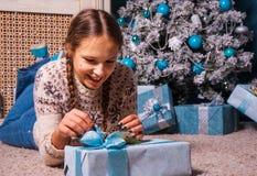La muchacha miente cerca de un árbol de navidad con la caja de regalo del regalo de Navidad Fotografía de archivo libre de regalías