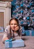 La muchacha miente cerca de un árbol de navidad con la caja de regalo del regalo de Navidad Foto de archivo libre de regalías