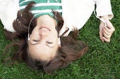 La muchacha miente con el jugador mp3 Imágenes de archivo libres de regalías