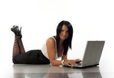 La muchacha miente con la computadora portátil Imagen de archivo
