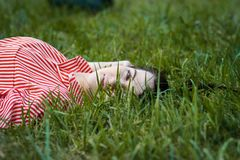 La muchacha miente en césped Fotos de archivo libres de regalías