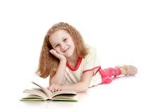 La muchacha miente en el piso y la lectura de un libro Foto de archivo