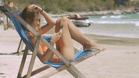 La muchacha miente en el sillón de madera contra la resaca de la onda