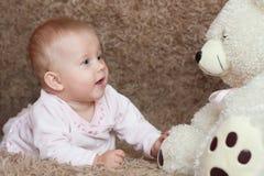 La muchacha miente en la alfombra junto con peluche Imagen de archivo
