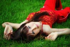 La muchacha miente en la hierba Fotos de archivo