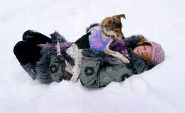 La muchacha miente en la nieve con su perro preferido Entertai del invierno imagen de archivo libre de regalías