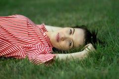 La muchacha miente en un césped Imagen de archivo