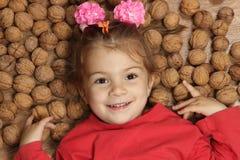 La muchacha miente en un piso en un montón de nueces Imagen de archivo