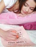 la muchacha miente en una cama y escribe la letra de amor Foto de archivo