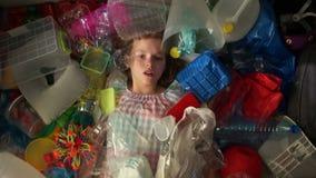 La muchacha miente en una pila de basura multicolora, una bolsa de plástico se cae encima de ella El problema de la contaminación metrajes
