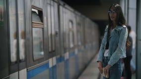 La muchacha mira alrededor, colocándose en la plataforma, pasando el tren, cámara lenta almacen de metraje de vídeo