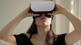 La muchacha mira cuidadosamente algo en los vidrios 3D metrajes