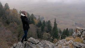 La muchacha mira del acantilado abajo lento-MES de la montaña almacen de metraje de vídeo