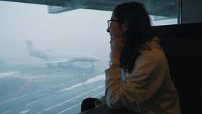 La muchacha mira el avión del terminal de aeropuerto almacen de video
