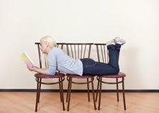 La muchacha mira el libro que miente en tres sillas Foto de archivo libre de regalías