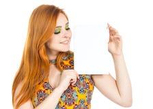 La muchacha mira el papel en blanco Copyspace Cuesta que lleva de la muchacha Redheaded Imagen de archivo libre de regalías