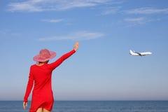 La muchacha mira el plano del vuelo Fotos de archivo