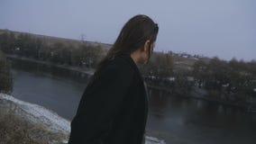 La muchacha mira el puente en el río durante las nevadas almacen de metraje de vídeo