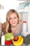 La muchacha mira el refrigerador interior Imagen de archivo libre de regalías