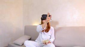 La muchacha mira el vídeo en vidrios de VR con las palomitas que se sientan en el sofá en dormitorio brillante por la tarde almacen de metraje de vídeo