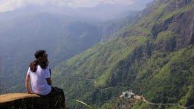 La muchacha mira el valle de un pico almacen de metraje de vídeo