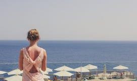 La muchacha mira en la distancia en el mar en un día de verano caliente imagenes de archivo