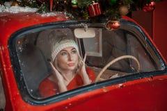 La muchacha mira en el espejo en el coche fotografía de archivo
