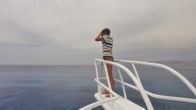 La muchacha mira en el mar en un yate Imagen de archivo libre de regalías