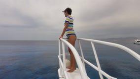 La muchacha mira en el mar en un yate Foto de archivo libre de regalías