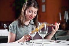La muchacha mira en el menú en café Imagen de archivo libre de regalías