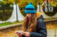 La muchacha mira en la tableta lee pensativamente las noticias de Internet Foto de archivo