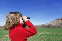 La muchacha mira en prismáticos Foto de archivo