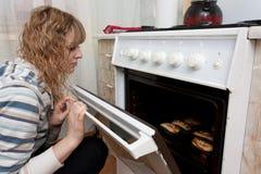 La muchacha mira en un horno fotos de archivo