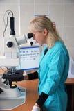 La muchacha mira en un microscopio Foto de archivo libre de regalías