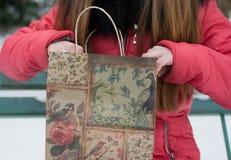 La muchacha mira en un paquete del regalo Tiempo de la Navidad, invierno Fotos de archivo