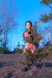 La muchacha mira a escondidas hacia fuera de detrás el árbol Imagenes de archivo