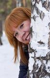 La muchacha mira a escondidas hacia fuera de detrás el abedul Fotos de archivo libres de regalías