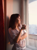 La muchacha mira fuera de la ventana imagenes de archivo