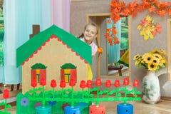 La muchacha mira hacia fuera de detrás el paisaje una casa de campo en el matinée en guardería Fotografía de archivo