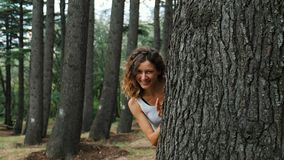 La muchacha mira hacia fuera de detrás un árbol y sonrisas metrajes
