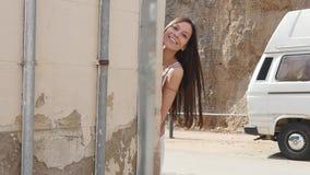 La muchacha mira hacia fuera de a la vuelta de la esquina, alegre, con humor almacen de metraje de vídeo