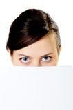 La muchacha mira hacia fuera debido a el papel Fotografía de archivo libre de regalías