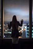 La muchacha mira hacia fuera la ventana Fotos de archivo