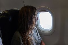 La muchacha mira hacia fuera la ventana del avión fotos de archivo libres de regalías