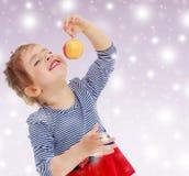 La muchacha mira la manzana Foto de archivo libre de regalías