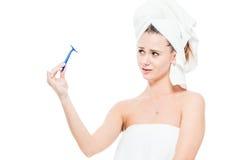 La muchacha mira la maquinilla de afeitar con negligencia en un blanco Imagen de archivo