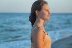La muchacha mira la puesta del sol del mar Imagen de archivo