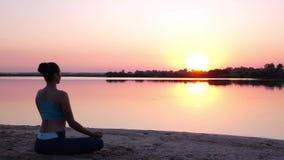 La muchacha mira la puesta del sol y medita almacen de metraje de vídeo