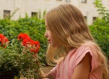 La muchacha mira las flores Imagen de archivo libre de regalías