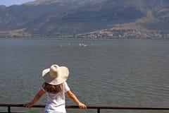 La muchacha mira los cisnes en el lago Ioannina Imagen de archivo libre de regalías